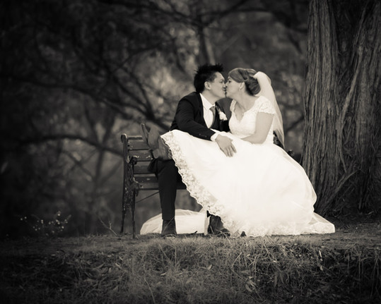 black and white image of a groom kissing bride on a bench