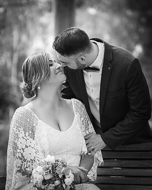 Groom leaning over to kiss bride on bench in black and white