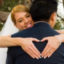 colour image of bride making a heart shape on husbands back