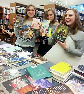 High School kids showing books bought with grant funds