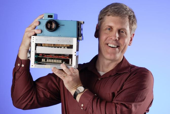 "Steven Sasson with his ""hand Held"" digital camera"