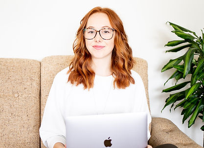 A young entrepreneur sitting with her laptop smiling at the camera
