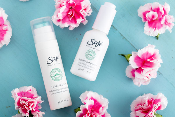 Product photo of skincare products surrounded by pink and white flowers on a bright blue background