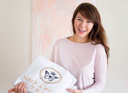 An entrepreneur with a big smile shows off some of her sweaters that she sells.