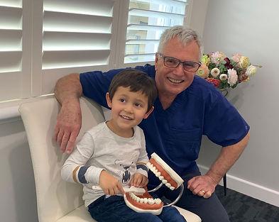 boy-brushing-teeth-with-smiling-dentist-