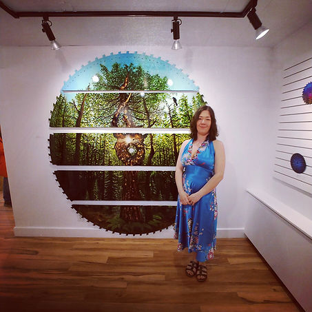 "Canadian Visual Artist Michelle C Spragg stands proudly in front on her latest works, See the Forest for the Trees.  She looks small compared to this giant 83"" saw blade thatshe has given new life to - by upcycling and adourning with alcohol inks, acrylics and resin.  Multidimensional and profoundly moving.  An astonishing piece of art!"