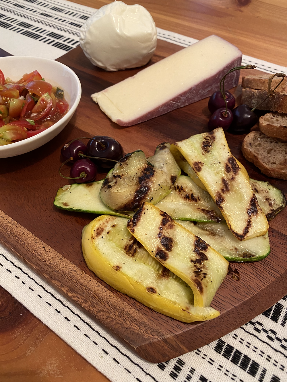 Picture of a platter with cheese, zucchini, whole grain baguette, cherries, and balsamic tomato bruchetta