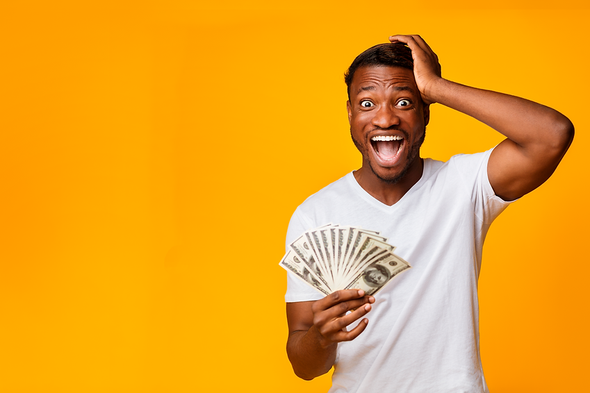 Young African American man on a yellow backdrop holding a fan of money