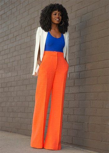 smart casual fashion outfit, woman wearing orange pants and white cape jacket
