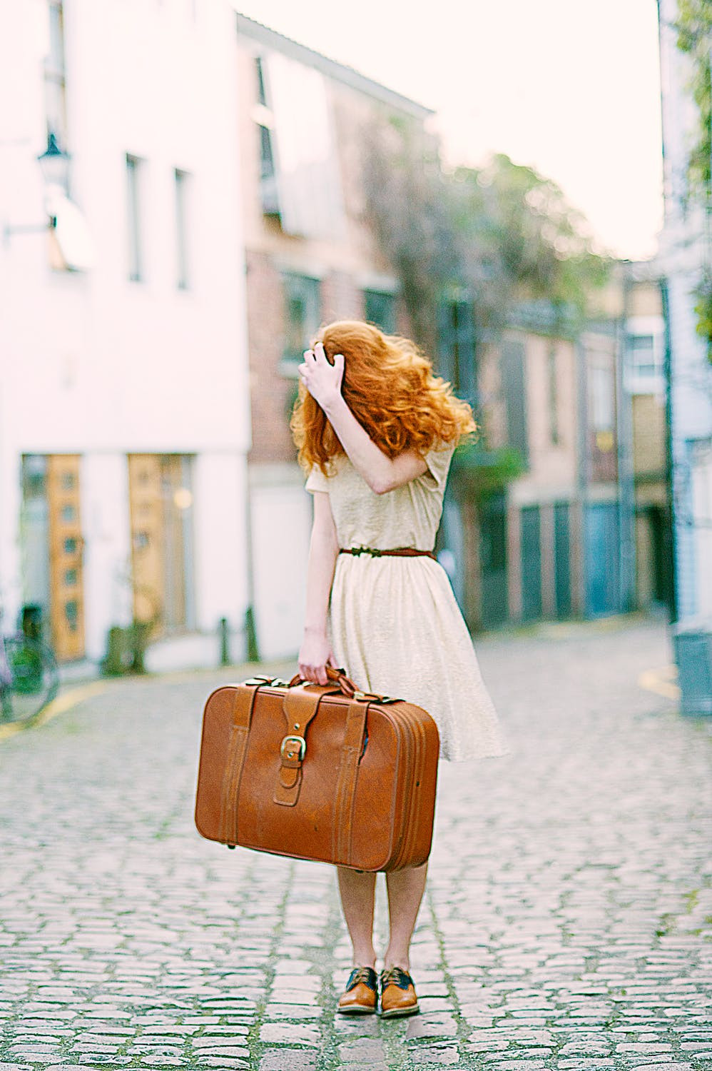woman carrying old fashioned trunk style suitcase