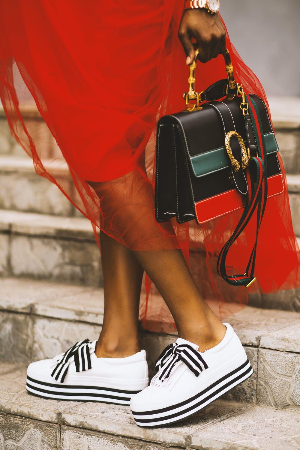 street style image of sports fashion sneakers and leather handbag