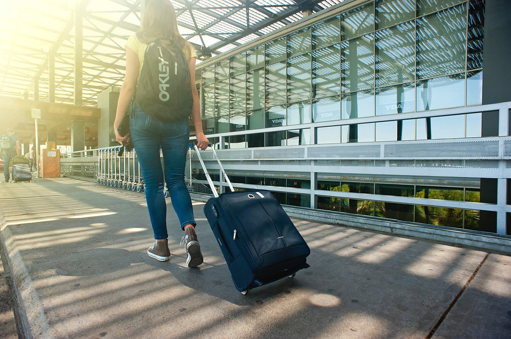 woman trailing suitcase at airport