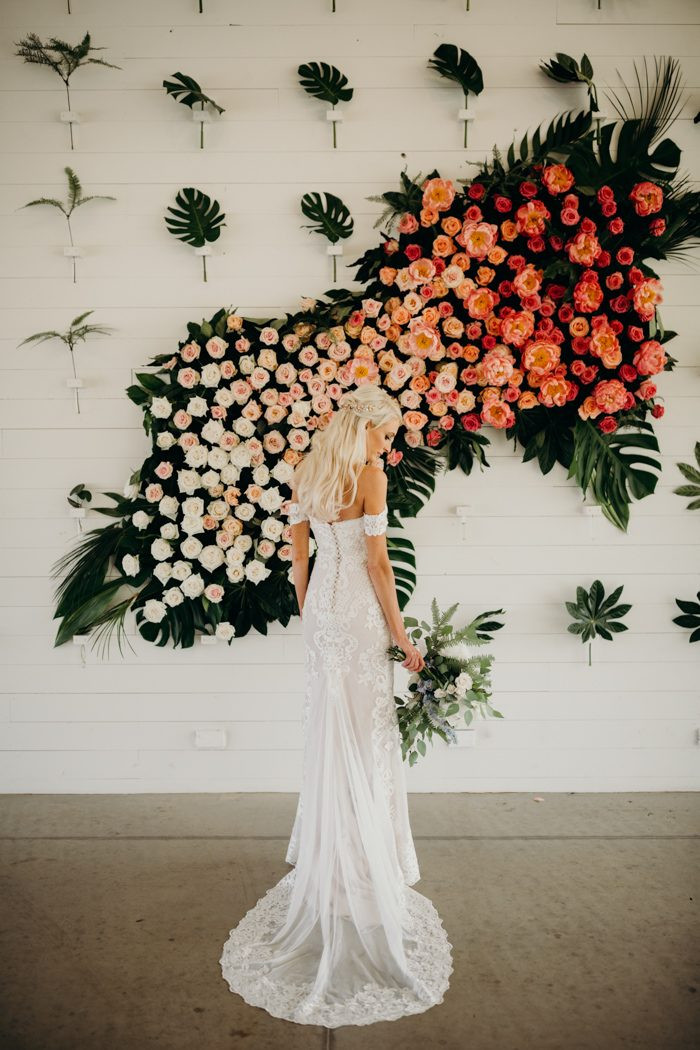 floral wall for weddings, bride standing beside floral wall decoration