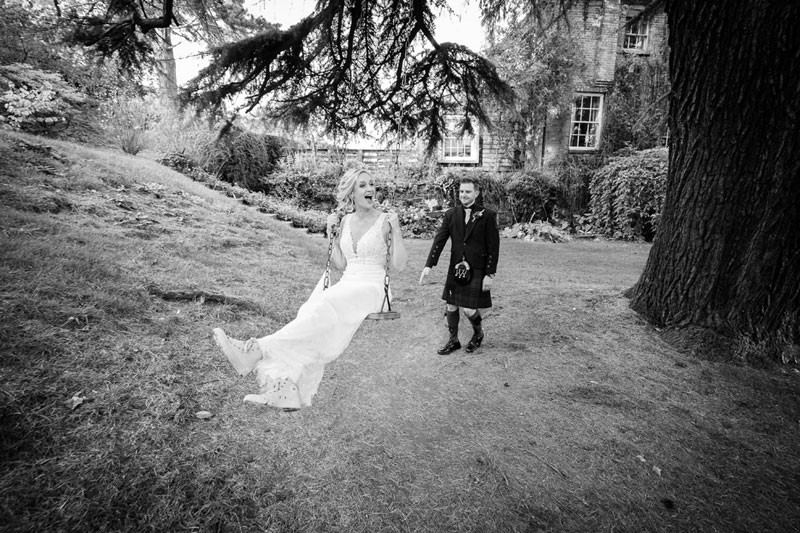 Bride and groom on swing at Walcot Hall