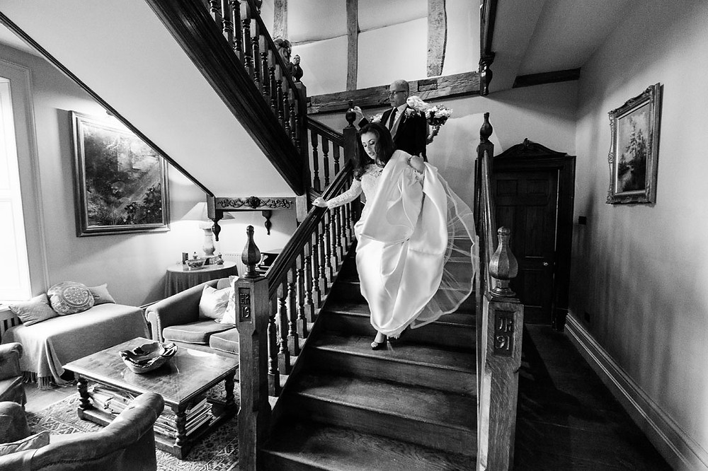 A bride descends the staircase at Dewsall Court