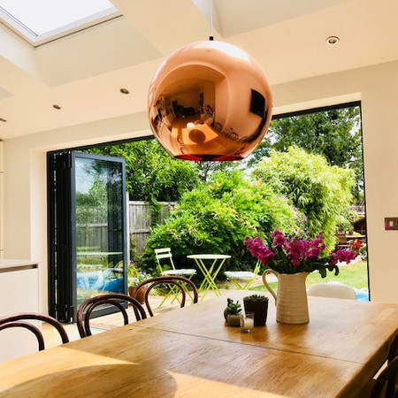 Open plan kitchen with pendant light and bifold doors