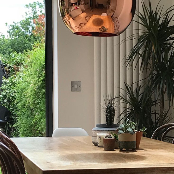 Tom Dixon pendant light over oak dining table