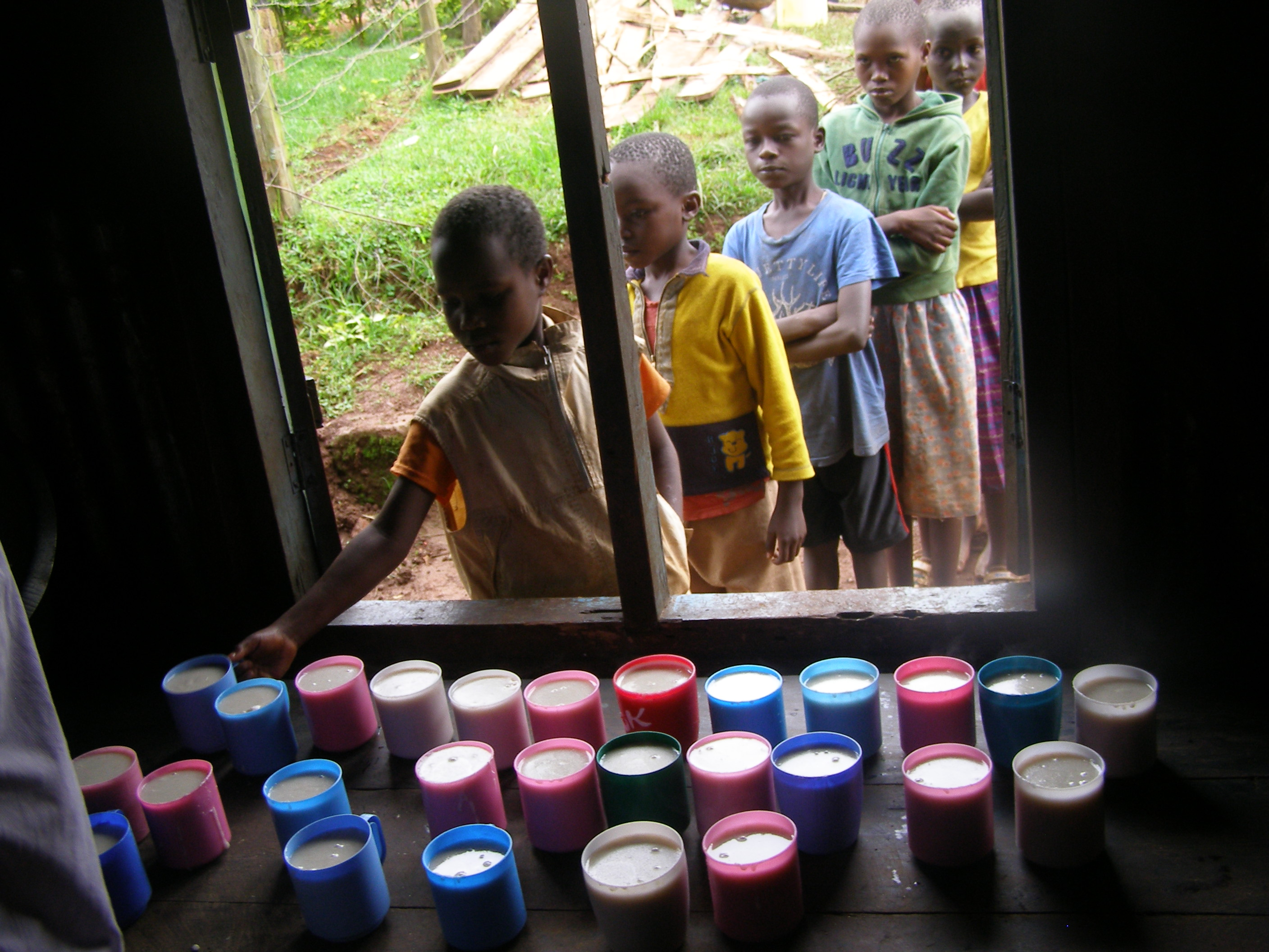 Children taking a cup of poridge