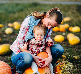 mother-and-daughter-sitting-on-pumpkins-