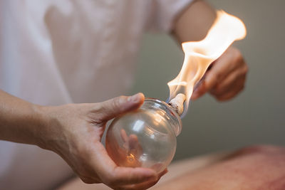 Woman preparing glass cup with fire for