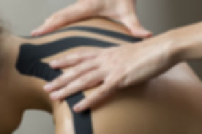 Physiotherapist putting on black kinesio