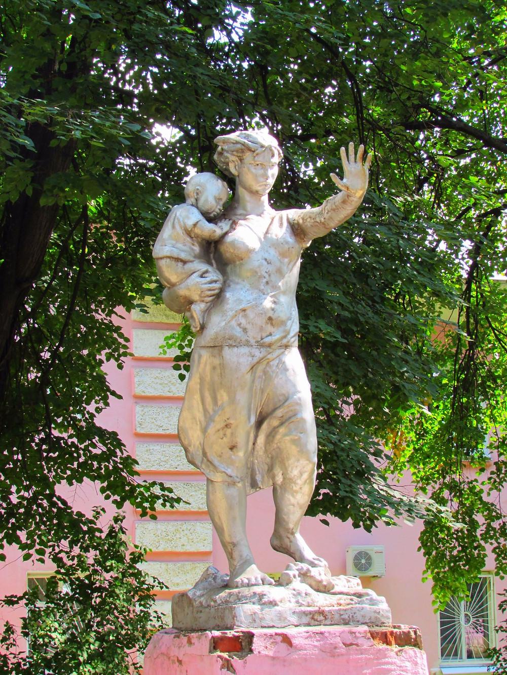 Суровый памятник женщине с младенцем