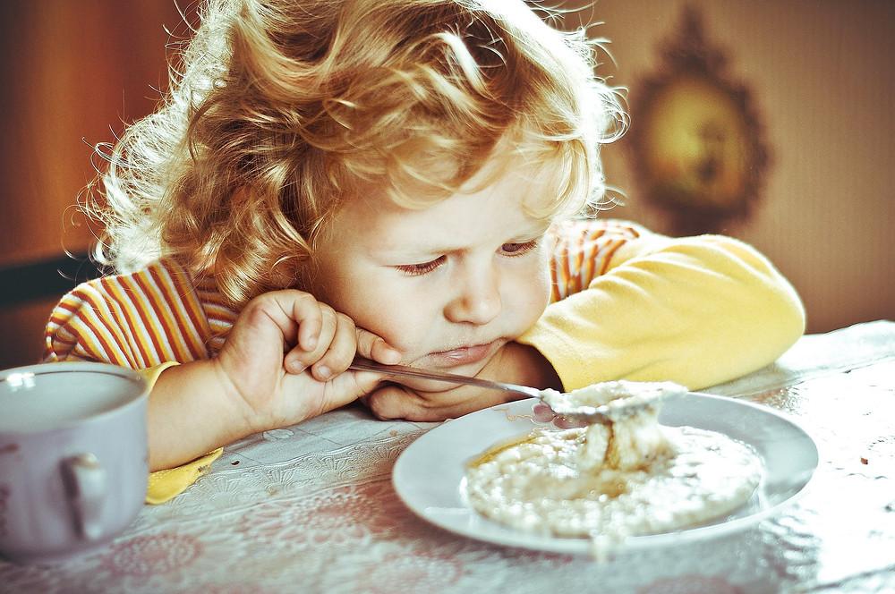 Девочка ест кашу