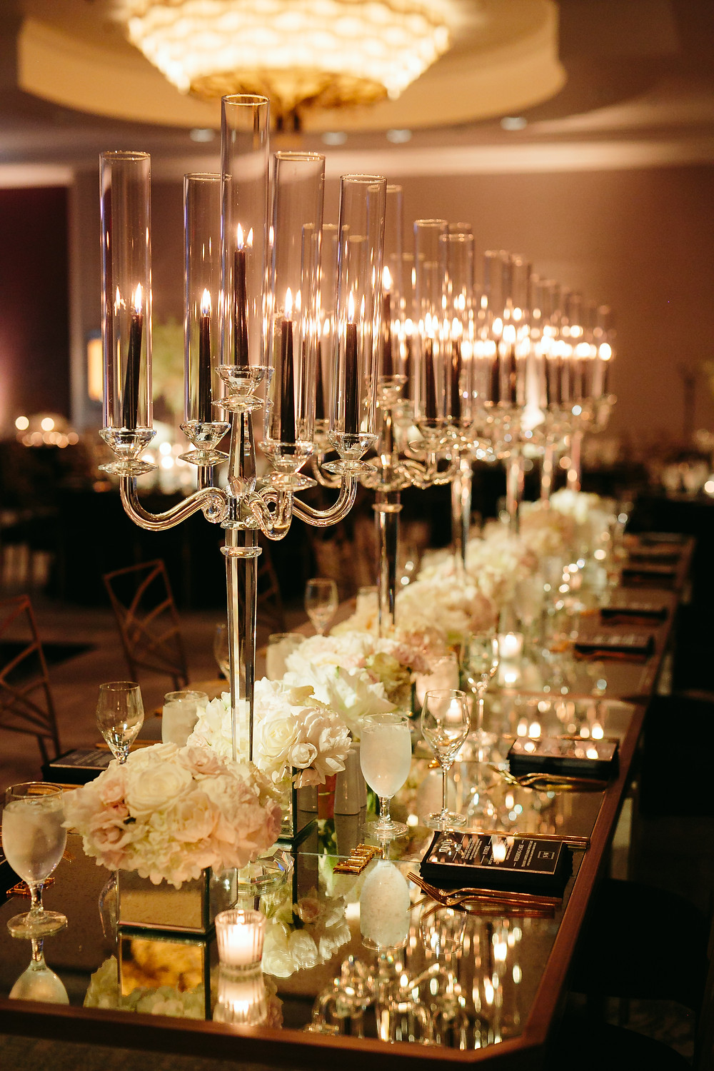 lots of small floral centerpieces with tall candelabras down the long rectangle setting