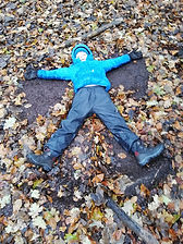 Child mking leafangel in leaves on the ground at WILD Foest School Session. Autumn leaves - browns and yellows.