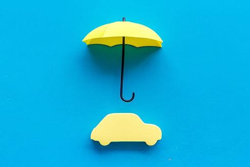 Car insurance. Automobile toy under umbr