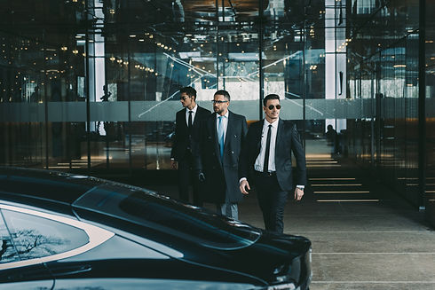 businessman and two bodyguards walking t