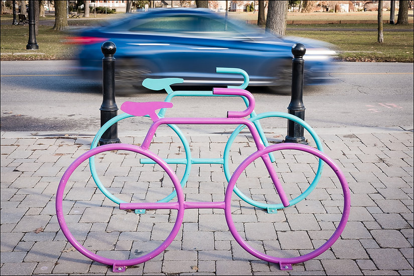 Two bicycle-shaped bike racks with a car in motion in the background