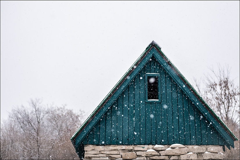 Snow falls gently on a replica stone mill at Churchill Park, Cambridge Ontario Canada