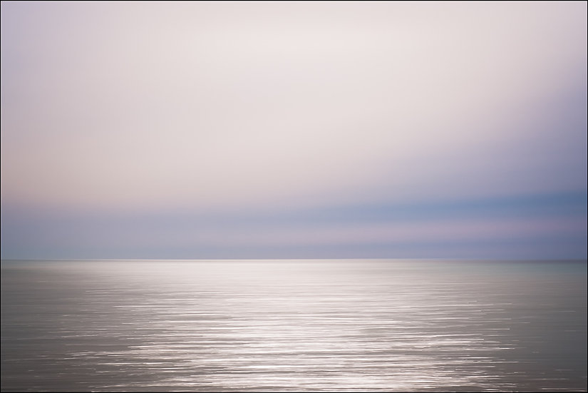Abstract photograph of the horizon in which the glints of sunlight on the water's surface are stretched into horizontal lines