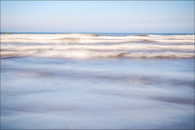 Abstract photograph of blurred waves cresting atop a blue body of water