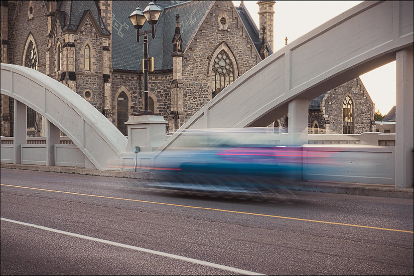 A car in motion across a bridge with a stone church in the background