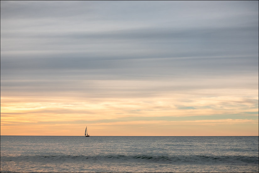 A single boat sailing in the distance during sunset at the beach