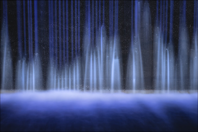 Abstract photograph of vertical streaks of blue water flowing into a pool