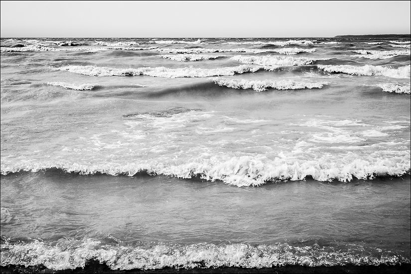 Black and white photograph of waves crashing into the shoreline