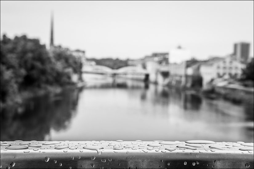 Black and white photo of rain drops on a railing with an out-of-focus Galt cityscape in the background, Cambridge Ontario