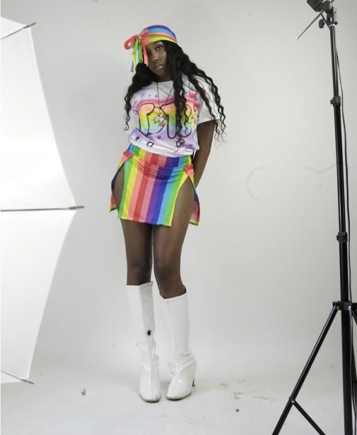 """Promoting her new merchandise on instagram, YBT encourages fans to purchase their """"Tots Tees"""" and pop out. YBT is sporting her T-shirt paired with a rainbow mini skirt and a matching durag. The go-go boots of this outfit make this colorful fit pop."""