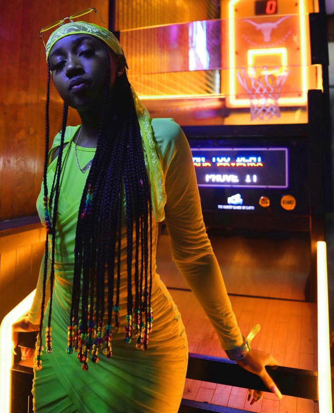 During her stay in Austin, TX, YBT had a mini-shoot in an arcade. We love how this tight-fitted yellow dress accentuates her figure in this shot. The yellow lace headscarf and rainbow beads on her braids are a great addition to this outfit.
