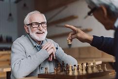 happy-senior-men-playing-chess-in-bar-3U