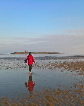 woman on Skerries beach in front of island