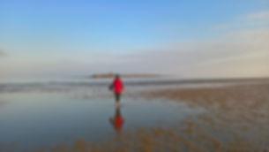 girl in red on skerries beach