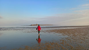 Girl walks along Skerries beach on a clear winter's day