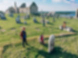 sightseers at the Clonmacnoise cemetery with cathedral in background