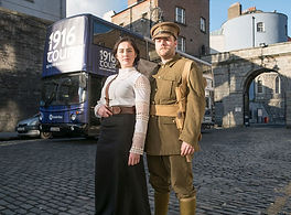 actor guides in front of 1916 tour bus