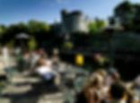 People drinking in Riverside Hotel terrace looking at Kilkenny Castle