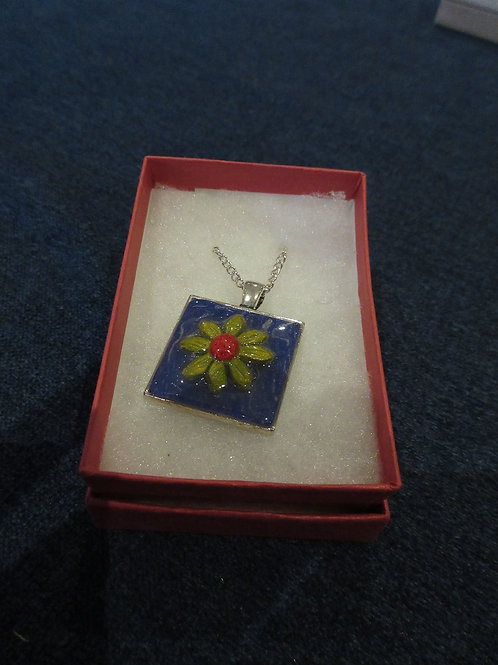 Artisan polymer clay set pendent with a decorative lime green daisy flower